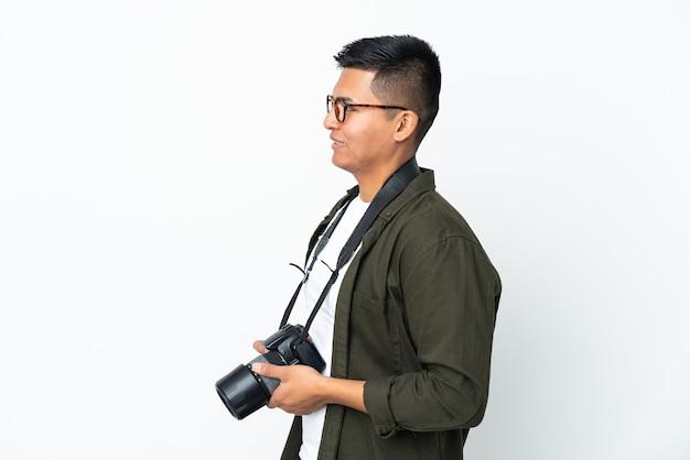 Молодой эквадорский фотограф изолирован на белом фоне, глядя в сторону