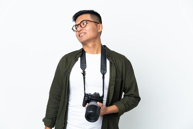 Молодой эквадорский фотограф изолирован на белом фоне, глядя в сторону и улыбается