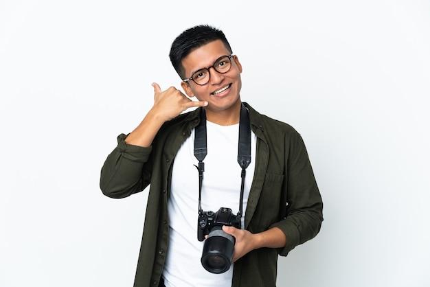 電話のジェスチャーを作る白い背景で隔離の若いエクアドルの写真家。コールバックサイン