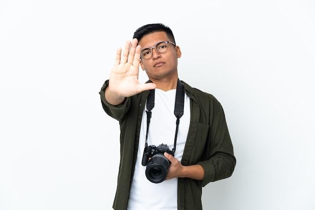 중지 제스처를 만드는 흰색 배경에 고립 된 젊은 에콰도르 사진 작가