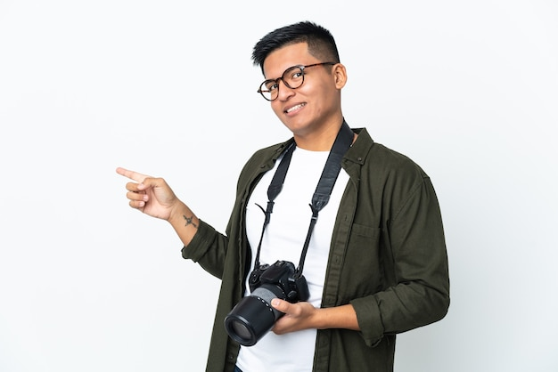 Молодой эквадорский фотограф изолирован на белом фоне, указывая пальцем в сторону