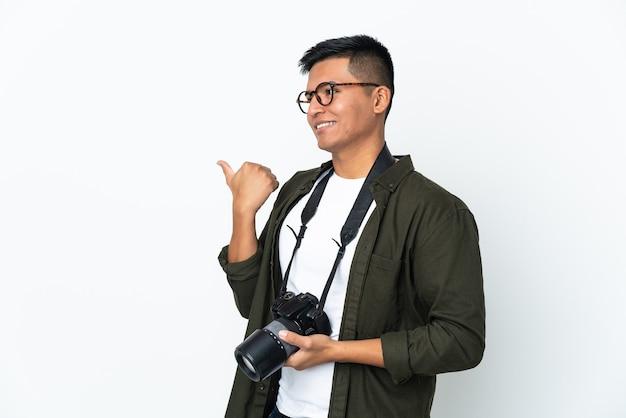 Молодой эквадорский фотограф изолирован на белом фоне, указывая в сторону, чтобы представить продукт