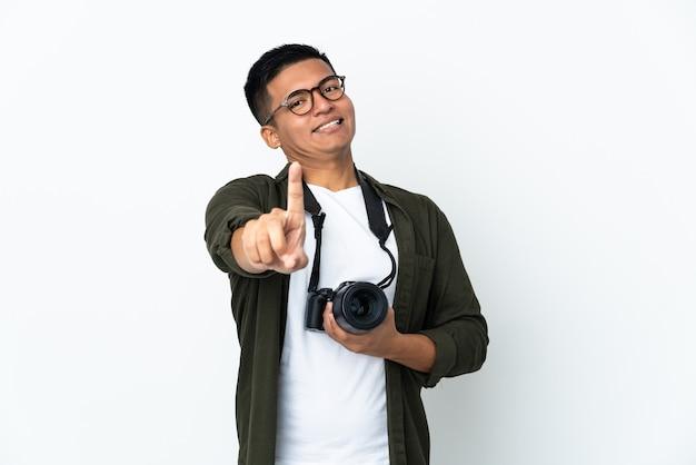 Молодой эквадорский фотограф изолирован на белом фоне, показывая и поднимая палец