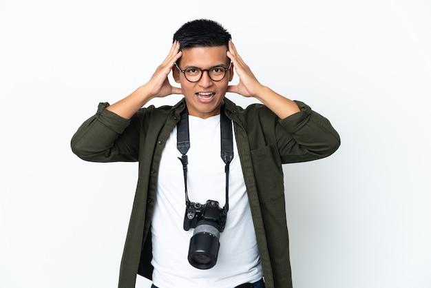 Молодой эквадорский фотограф изолирован на белом фоне с удивленным выражением лица