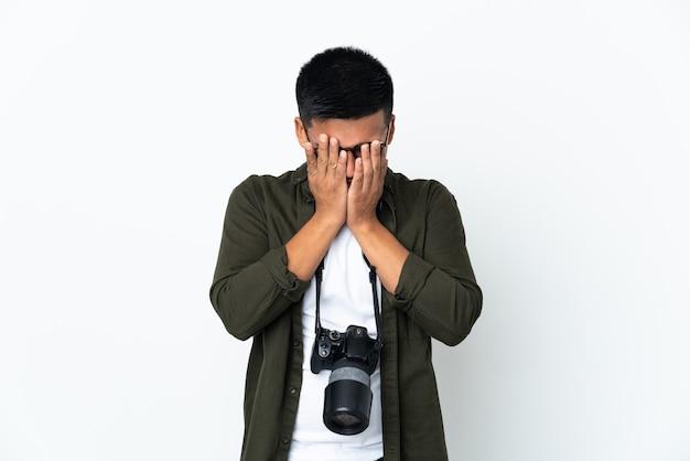 Молодой эквадорский фотограф изолирован на белом фоне с усталым и больным выражением лица