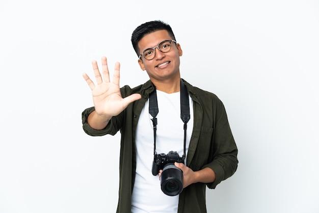 Молодой эквадорский фотограф изолирован на белой стене, считая пять пальцами