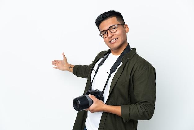 와 서 초대를 위해 손을 옆으로 확장 흰 벽에 고립 된 젊은 에콰도르 사진 작가