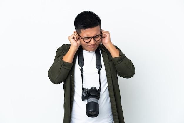 欲求不満と耳を覆っている白い壁に孤立した若いエクアドルの写真家