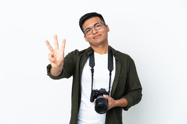 젊은 에콰도르 사진 작가는 흰 벽에 행복하고 손가락으로 세 세에 고립