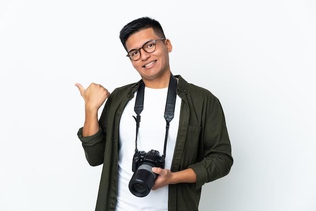 제품을 제시하기 위해 측면을 가리키는 흰 벽에 고립 된 젊은 에콰도르 사진 작가