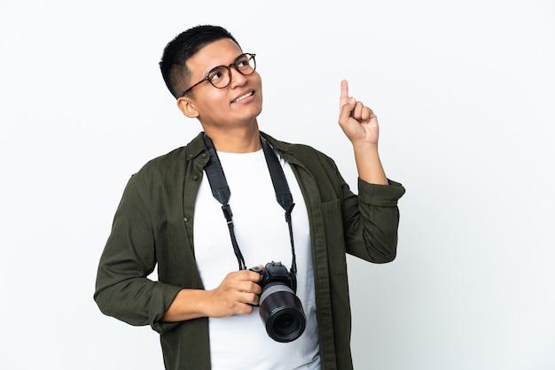 좋은 아이디어를 가리키는 흰 벽에 고립 된 젊은 에콰도르 사진 작가