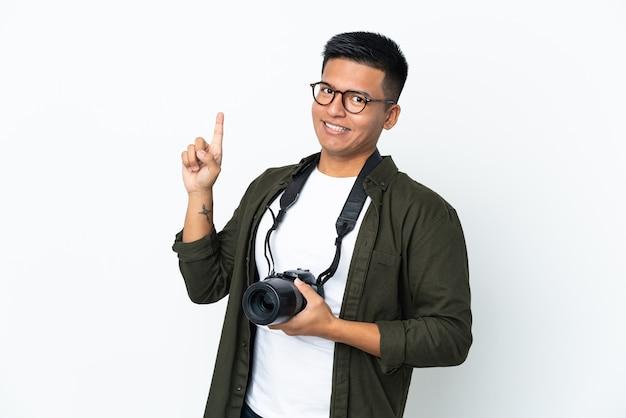 흰 벽에 고립 된 젊은 에콰도르 사진 작가는 최고의 기호에 손가락을 보여주는