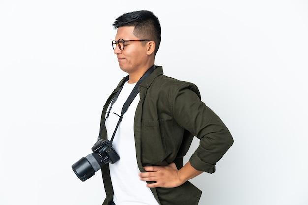 努力したために腰痛に苦しんでいる白い壁に孤立した若いエクアドルの写真家