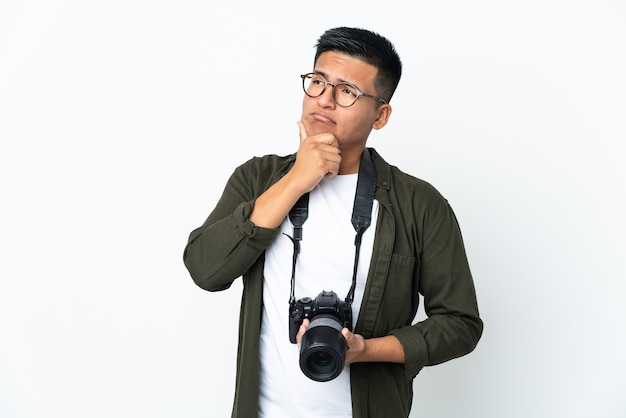 Young ecuadorian photographer isolated on white wall having doubts