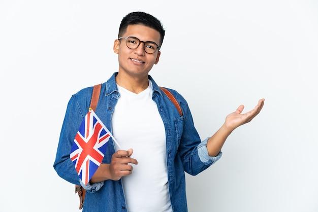 와 서 초대에 대 한 측면으로 손을 확장 흰색 배경에 고립 된 영국 국기를 들고 젊은 에콰도르 여자