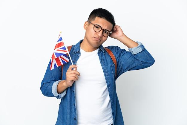 의심을 갖는 흰색 배경에 고립 된 영국 국기를 들고 젊은 에콰도르 여자