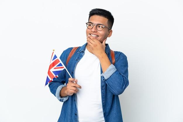 웃는 동안 찾고 흰색 배경에 고립 된 영국 국기를 들고 젊은 에콰도르 여자