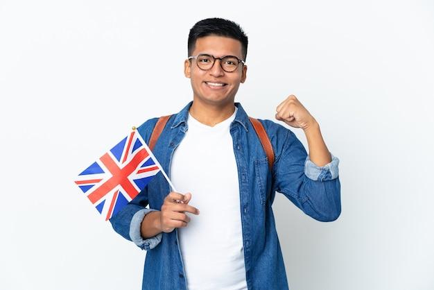 강한 제스처를 하 고 흰 벽에 고립 된 영국 국기를 들고 젊은 에콰도르 여자