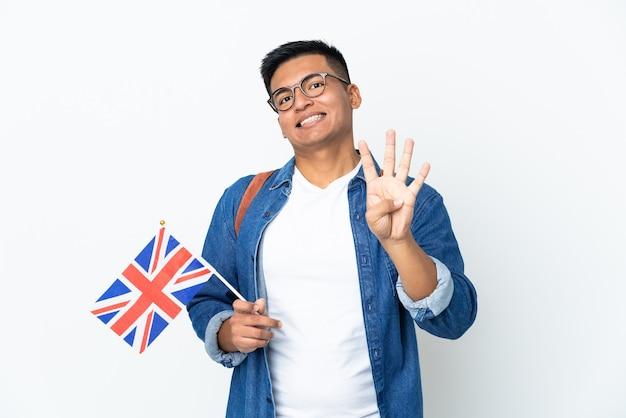 Молодая эквадорская женщина держит флаг соединенного королевства, изолированную на белой стене, счастлива и считает четыре пальцами