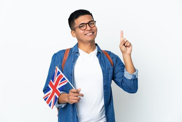 Молодая эквадорская женщина, держащая флаг соединенного королевства, изолированная на белой стене, показывает и поднимает палец в знак лучших