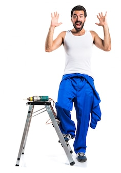 Young electrical technician with a drill doing surprise gesture