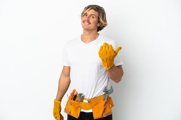 젊은 전기 금발 남자 손으로와 서 초대 흰색 배경에 고립. 와줘서 행복해