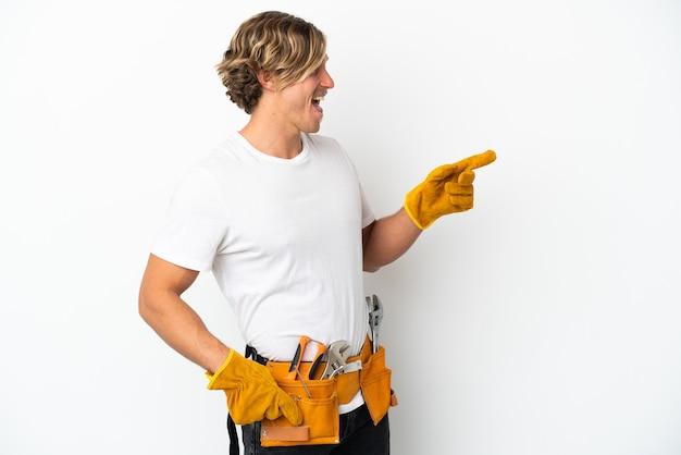 젊은 전기 금발의 남자는 측면에 손가락을 가리키고 제품을 제시하는 흰색 배경에 고립