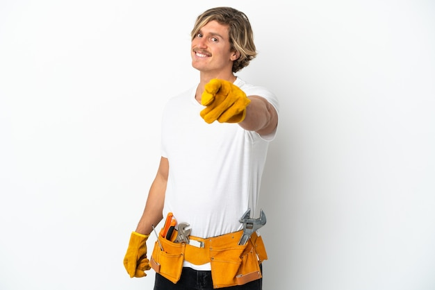 행복 한 표정으로 앞을 가리키는 흰 벽에 고립 된 젊은 전기 금발 남자