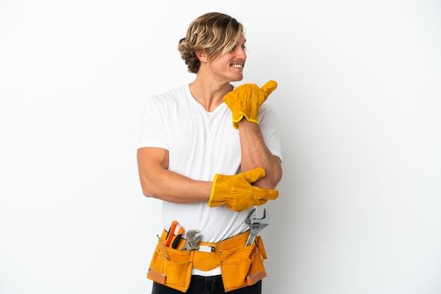 제품을 제시하기 위해 측면을 가리키는 흰 벽에 고립 된 젊은 전기 금발 남자