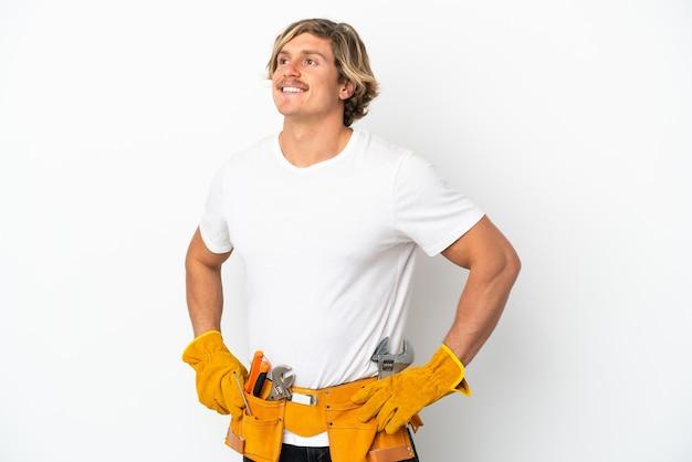 엉덩이에 팔을 포즈와 미소 흰 벽에 고립 된 젊은 전기 금발의 남자