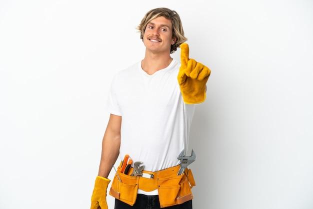 보여주는 손가락을 들고 흰 벽에 고립 된 젊은 전기 금발 남자