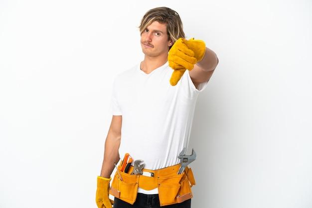 부정적인 표현으로 아래로 엄지 손가락을 보여주는 흰 벽에 고립 된 젊은 전기 금발 남자