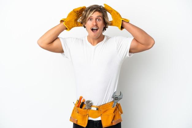 놀라운 표정으로 흰 벽에 고립 된 젊은 전기 금발 남자