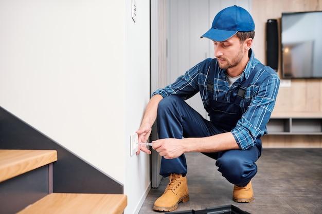 Молодой электрик из бытовой службы, стоя на корточках у стены, проверяя напряжение в розетке