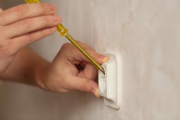 Молодой электрик устанавливает электрическую розетку на стену с помощью отвертки