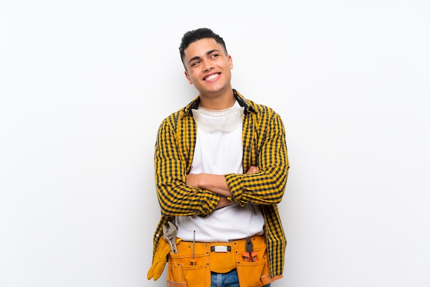 Young electrician man over isolated white wall looking up while smiling