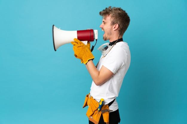 Молодой электрик на изолированной стене кричит в мегафон