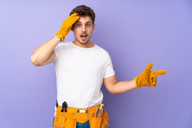 紫色の驚きと人差し指で孤立した若い電気技師の男