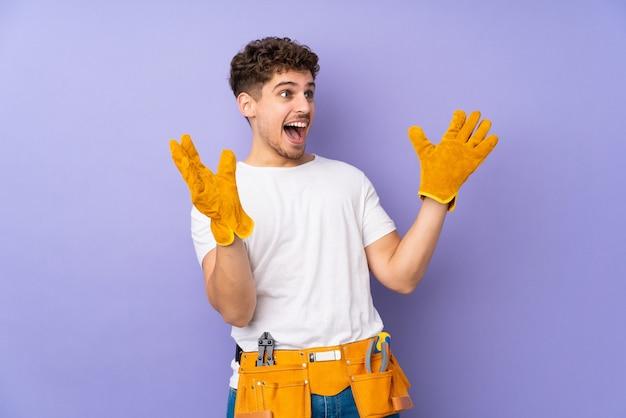 驚きの表情で紫に孤立した若い電気技師の男