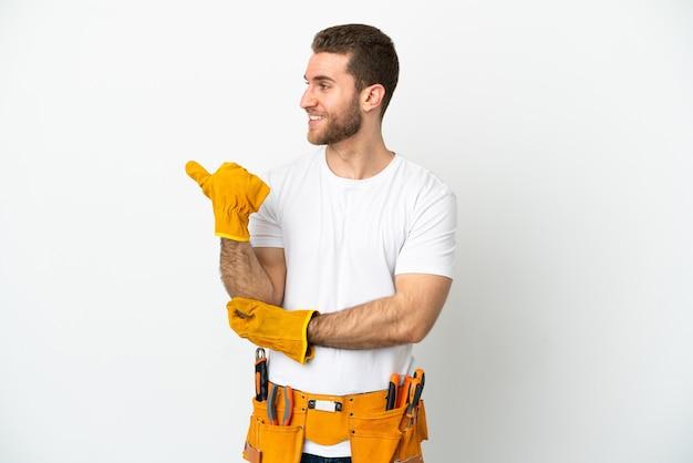 제품을 제시하기 위해 측면을 가리키는 격리 된 흰 벽 위에 젊은 전기 남자