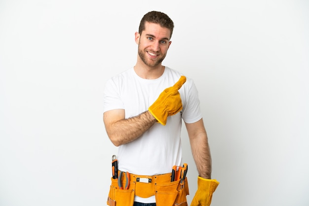 제품을 제시하기 위해 측면을 가리키는 고립된 흰색 벽 위에 젊은 전기 남자