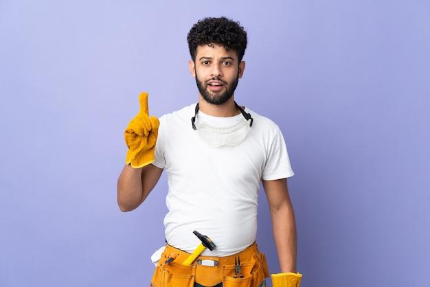 손가락을 가리키는 아이디어를 생각하는 보라색 배경에 고립 된 젊은 전기 모로코 남자