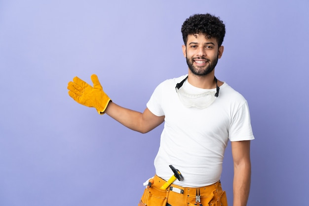 보라색 벽에 고립 된 젊은 전기 모로코 남자가 와서 초대하기 위해 손을 옆으로 확장