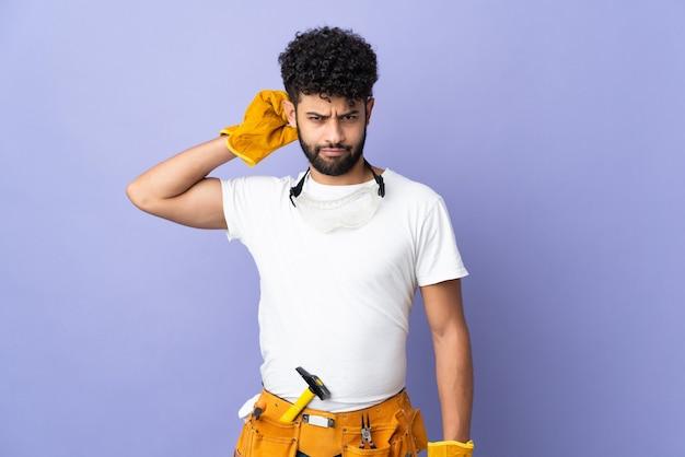 의심을 갖는 보라색 벽에 고립 된 젊은 전기 모로코 남자
