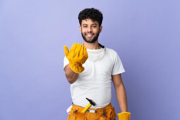 손으로와 서 초대 보라색 벽에 고립 된 젊은 전기 모로코 남자. 와줘서 행복해
