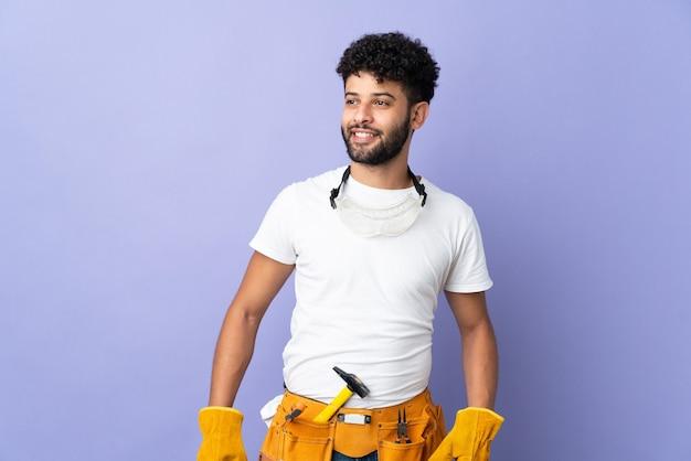 엉덩이에 팔을 포즈와 미소 보라색 벽에 고립 된 젊은 전기 모로코 남자