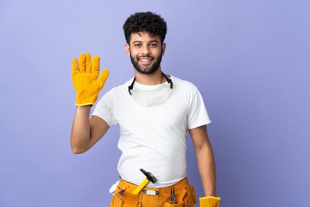 행복 한 표정으로 손으로 경례 보라색 벽에 고립 된 젊은 전기 모로코 남자