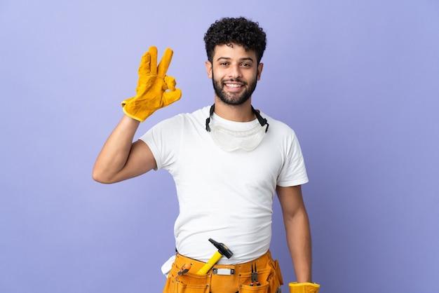 손가락으로 ok 사인을 보여주는 보라색 벽에 고립 된 젊은 전기 모로코 남자