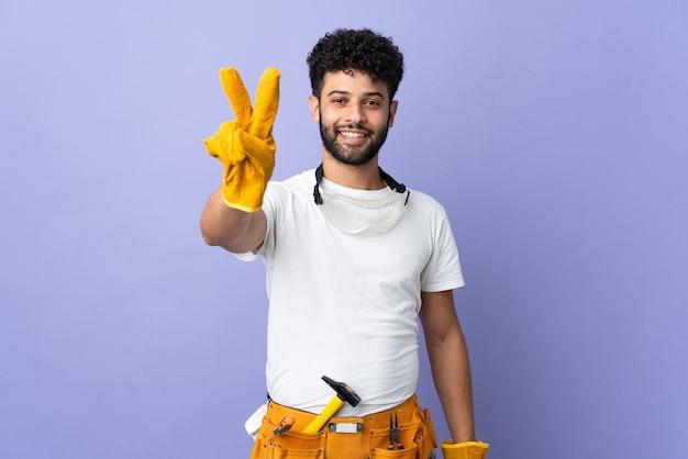 웃 고 승리 기호를 보여주는 보라색 벽에 고립 된 젊은 전기 모로코 남자