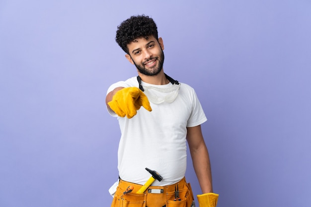 Young electrician moroccan man isolated on purple pointing front with happy expression
